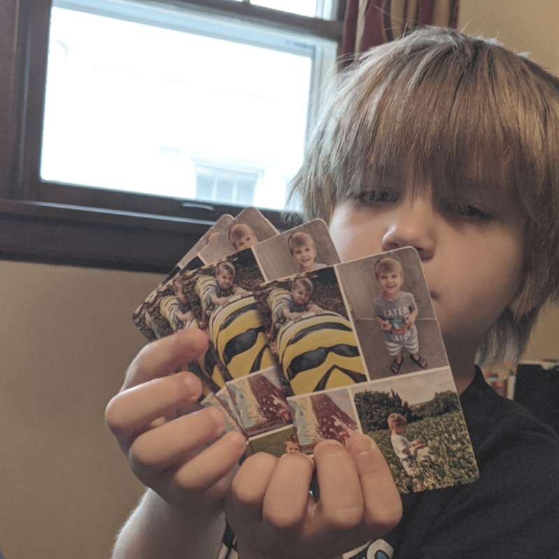 Young boy holding playing cards with photos on them